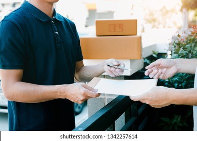 Young asian delivery staff holding the pen and documents submitting giving to the customer receiving the parcel at front house.