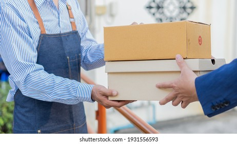 A young Asian deliveryman with a mailbox in a protective uniform, he provides service and the customer receives the front door.