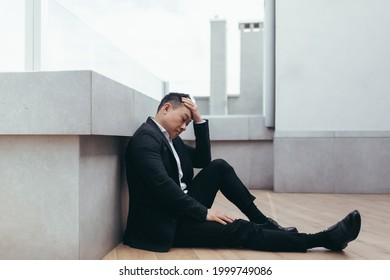 young asian depressed man sitting on outdoors street near office business center building. The upset male businessman lost his job due to the financial crisis and quarantine. Businessman has problems