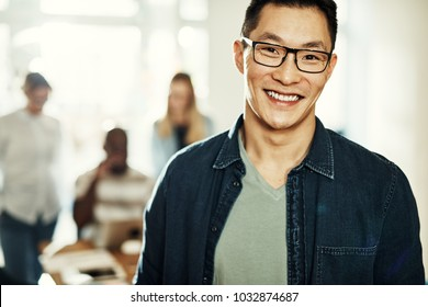 Young Asian designer wearing glasses and smiling confidently while standing in a modern office with colleagues in the background