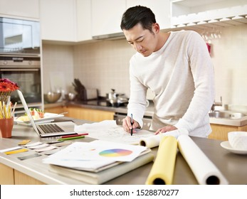 young asian designer working at home drawing on drafting paper on kitchen counter