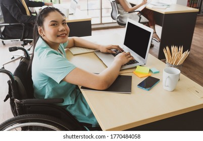 young asian disabled woman with smiling face sitting in the wheelchair and using computer to discuss project with her colleagues in the working office. disability and handicapped concept