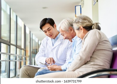 young asian doctor discussing test result and diagnosis with senior couple patients using digital tablet in hospital hallway