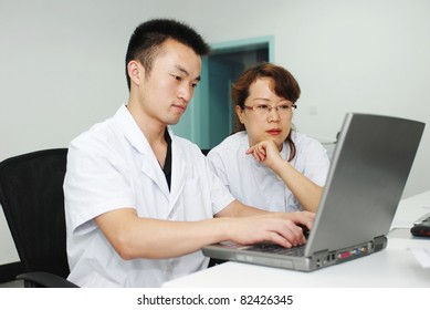 young asian doctor and nurse working with laptop