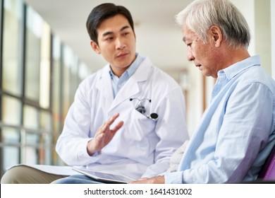 young asian doctor talking and explaining test result and diagnosis to demoralized elderly patient in hospital hallway