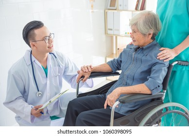 Young asian doctor touching patient hand and smiles at hospital