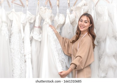 Young Asian dressmaker woman select the fabric and prepare for wedding dress cutting. Smiling to the camera.