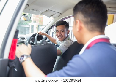 young asian driver smiling to his customer sitting on the back of the car