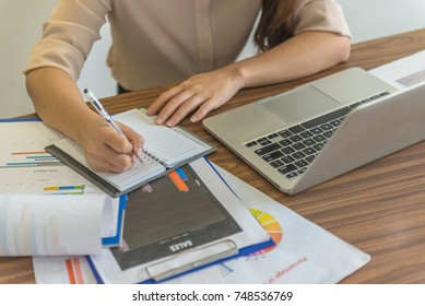 Young Asian employee writing notes