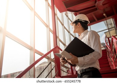 Young Asian Engineer or Architect holding files while wearing personal protective equipment safety helmet at construction site. Engineering, Architecture and building construction concepts