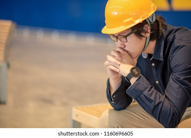 Young Asian engineer or architect man feeling tried and stressed while sitting on bench. depression from hard work concept