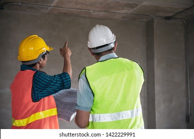 Young Asian engineer or building inspector checking interior building detail with male construction worker by using check list and drawing. Two building worker inspecting interior building.