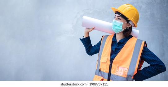 A young Asian engineer holds a white board sign for writing messages or announcements against a backdrop of concrete wall at the job site. Leader concept