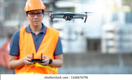 Young Asian engineer man flying drone over construction site. Using unmanned aerial vehicle (UAV) for land and building site survey in civil engineering project.