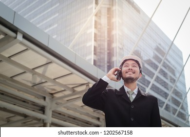 Young asian engineer man talking on mobile phone in modern building city