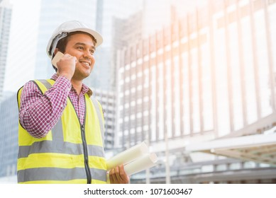 Young asian engineer talking on phone with paperwork on building background.
