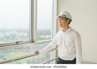 Young Asian engineer with white safety hard helmet for security equipment working