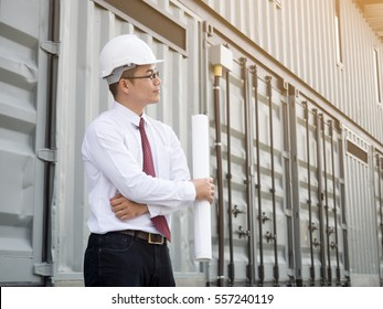 Young asian engineer/architect holding building drawing looking at factory plant. smart engineer for construction work concept