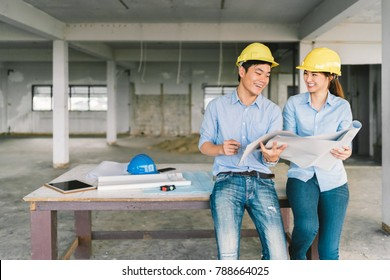 Young Asian engineers couple working together on building blueprint at construction site or factory. Civil engineering, industrial business partner, or home renovation service concept. With copy space