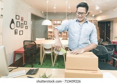 Young asian entrepreneur packing product into the box for his customers after received order at home office. Conceptual for startup small businesses starting own company and online marketing.