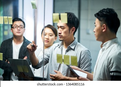 young asian entrepreneur of small company drawing a diagram on glass during team meeting discussing and analyzing business situation in office.
