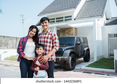 young asian family with kid in front of their house and car