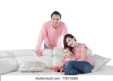 Young Asian family laughing together while sitting on the couch, isolated on white background