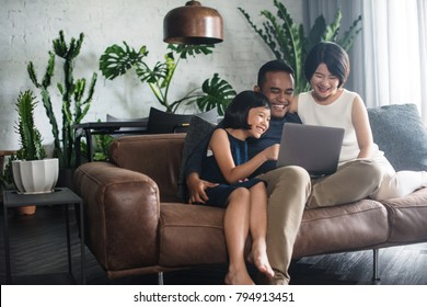 Young Asian family looking at the laptop together at home.