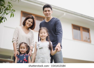 Young Asian family love, father mother and two daughter standing at outdoor in front of home. girl and parent looking at camera which smiling and felling happy and background is a white house.