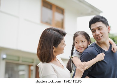 Young Asian family love, father mother and daughter standing playing and fun at outdoor in front of home. girl and father looking at mother which smiling and felling happy. background is white house.