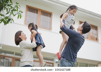 Young Asian family love, father mother and daughter standing playing and fun at outdoor in front of home. parent lift up daughter which smiling and felling happy. background is white house.