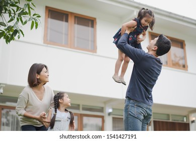 Young Asian family love, father mother and daughter standing playing and fun at outdoor in front of home. father lift up daughter which smiling and felling happy. background is white house.