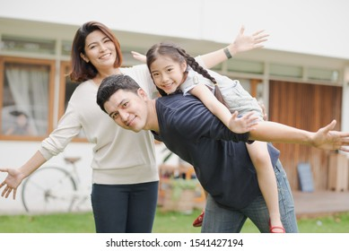 Young Asian family love, father mother and daughter standing playing and fun at outdoor in front of home. girl and parent looking at camera which smiling and felling happy. background is white house.