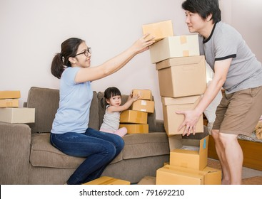 Young asian family man woman and girl packing cardboard box in the office SME business, family relocation moving house and small business, SME concept