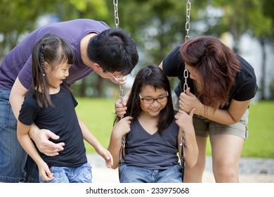 Young Asian family playing swing bonding in park