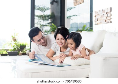 Young Asian family reading a book with daughter at home.