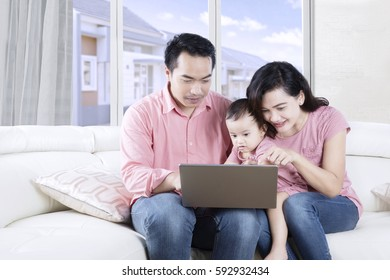 Young Asian family watching a movie on a laptop together while sitting on the couch