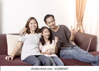Young asian family watching TV together at home and having fun together.