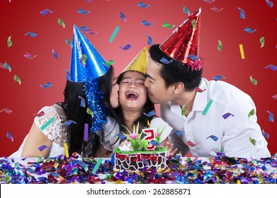 Young asian family wearing birthday cap and kissing the child in birthday party