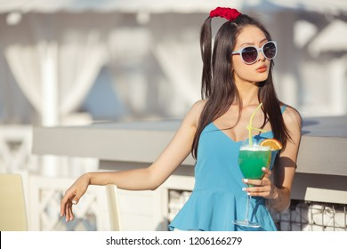 Young asian fashion woman drinking cocktail in a beach bar. Cheerful attractive blonde woman in trendy sunglasses and dress smiling and drinking cocktail outdoor. Happy female enjoys summer time in
