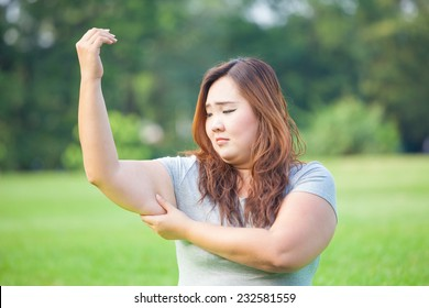 Young asian fat woman checking her arm fat