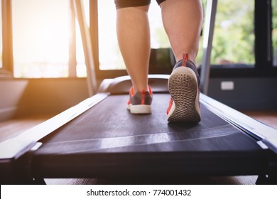 Young asian fat woman workout at gym,walking or running on treadmill equipment,exercise and relaxing concept.