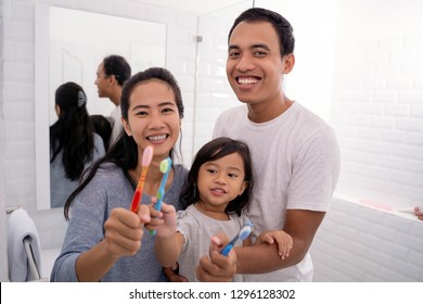 young asian father and mother with kid showing their tooth brush to camera and smile