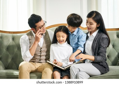 young asian father and mother and two children sitting on couch reading book together in family living room at home