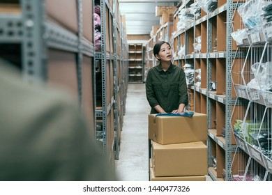 young asian female delivery postman pushing cart walking in storehouse of company. woman moving lots of cardboard boxes while doing stocktaking in warehouse. girl staff in uniform work in stockroom