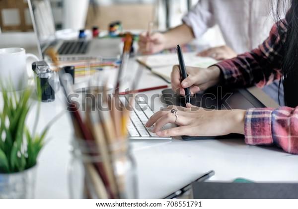 Юная азиатская женщина-дизайнер использует графический планшет во время работы с компьютером в студии или офисе.
