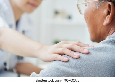 Young Asian Female doctor putting her hand on senior male patient shoulder for comforting in medical room at the hospital. Diseases, Ill, Symptom, Health care talking of Elderly.