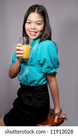 A young asian female drinking orange juice
