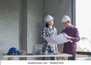Young Asian female engineer or architect checking interior building detail with male construction worker by using check list and drawing showing woman power or leadership ability.