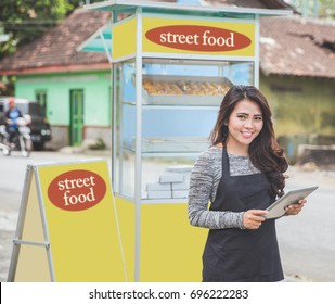young asian female entrepreneur with her small business food stall. promoting online using tablet pc